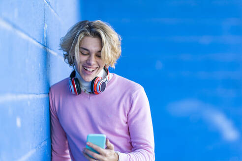 Happy fashionable young man using mobile phone while leaning on blue wall - GGGF00481