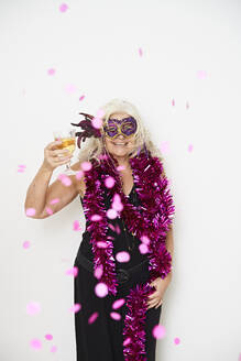 Happy fashionable senior woman with glass wearing masquerade mask against white background - JAHF00024
