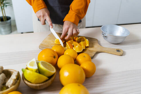 Woman cutting orange fruit for preparing fresh juice while standing in kitchen at home - GIOF10041