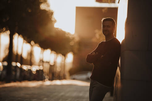 Man leaning on wall with arms crossed during sunset in city - GMLF00930