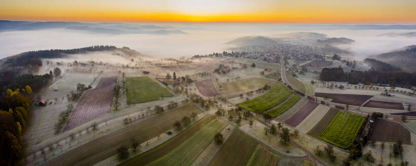 Germany, Baden-Wurttemberg, Berglen, Drone view of countryside fields at foggy autumn sunrise - STSF02739