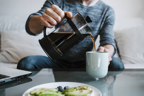Man holding coffee maker while pouring coffee in coffee cup sitting at home - EBBF01788