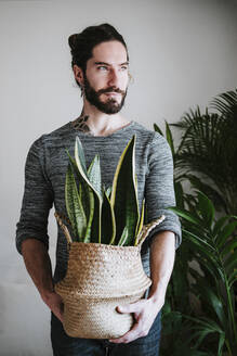 Young man holding Sansevieria plant while standing at home - EBBF01815