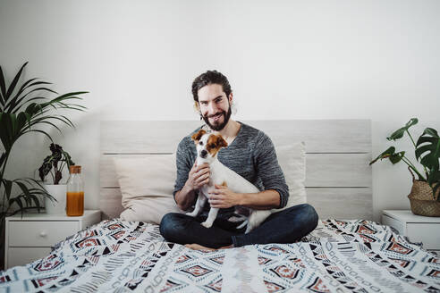 Handsome man sitting with dog on bed at home - EBBF01836