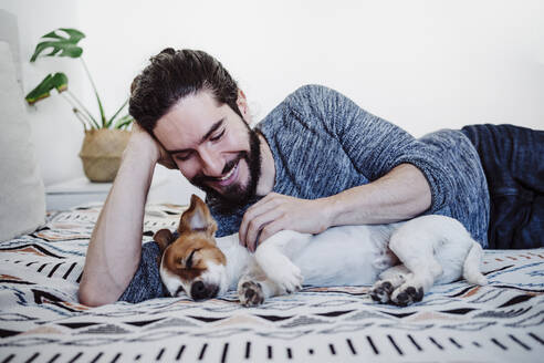 Young man smiling while looking at dog sleeping on bed at home - EBBF01839