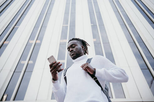 Young businessman using mobile phone against skyscraper in city - EBBF01862