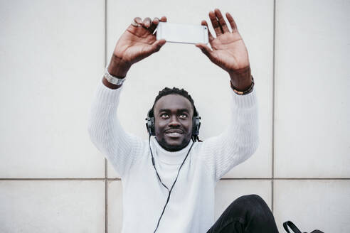 Smiling young man taking selfie while listening music against white wall - EBBF01874
