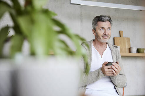 Thoughtful man holding coffee cup while sitting at home - FMKF06917