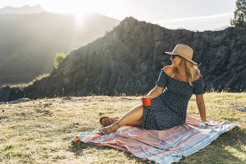 Smiling woman with coffee cup day dreaming while sitting on picnic blanket on sunny day - MPPF01330