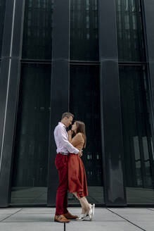 Heterosexual couple looking at each other while embracing against building - OGF00673