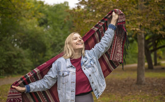 Happy woman with scarf standing in autumnal park - BFRF02332