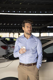 Male entrepreneur with hand in pocket holding mobile phone while standing at parking lot - IFRF00195