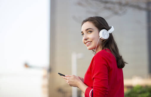 Smiling woman listening music through headphones while holding smart phone - JCCMF00251