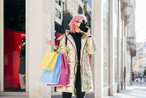 Woman wearing protective face mask talking on mobile phone while standing with shopping bags in city - MARF00043