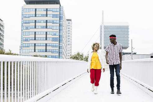 Mid adult woman and man talking while walking on bridge in city - XLGF00924