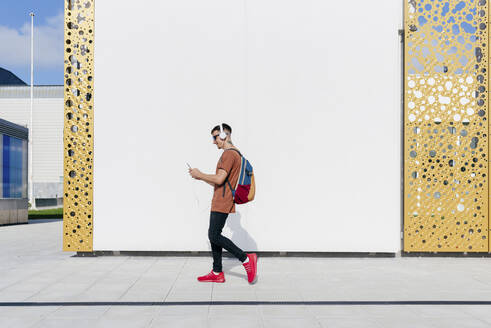 Young man wearing headphones using mobile phone while walking against wall - MARF00048