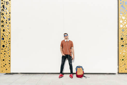 Man with backpack and headphones standing with hands in pockets against wall - MARF00051