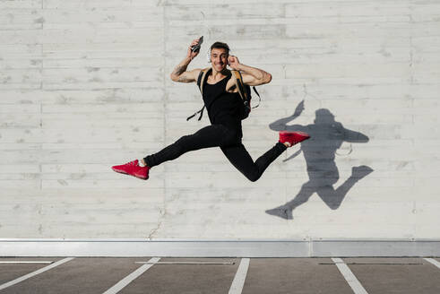 Carefree young man with mobile phone and headphones carrying backpack while jumping against wall - MARF00060