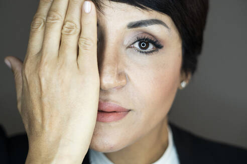 Portrait of businesswoman covering face with hand - GIOF10144