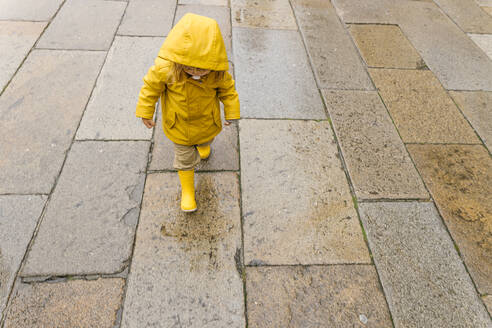 Full body of cropped unrecognizable cute little kid wearing bright yellow raincoat and rubber boots standing on wet pavement - ADSF19291