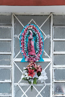 Virgin Mary figurine with flowers on metal grate - JMPF00751
