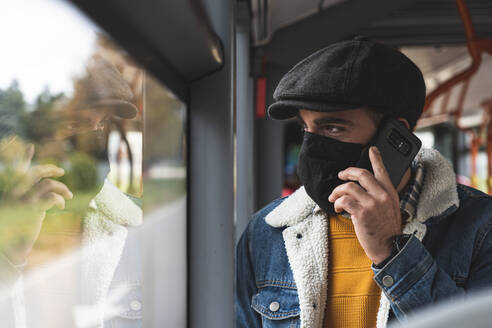 Commuter wearing protective face mask on phone call in bus - JAQF00028