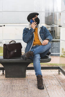 Commuter on phone call looking away while sitting at bus stop during COVID-19 - JAQF00040