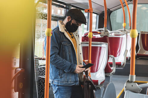 Commuter using smart phone while standing by pole during COVID-19 - JAQF00043