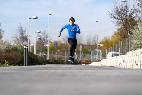 Sportsman running with dedication on footpath in public park on sunny day - GGGF00507