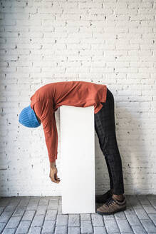 Mid adult man bending over pedestal against white brick wall - RCPF00488
