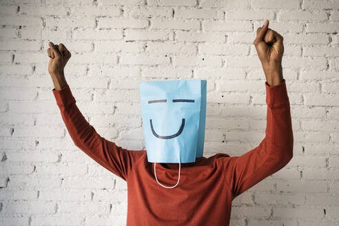 Man wearing blue paper bag while dancing against white brick wall - RCPF00539