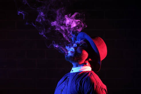 Side view of stylish African American male in hat and sunglasses standing on black background in studio with neon illumination and smoking vape while exhaling steam - ADSF19451