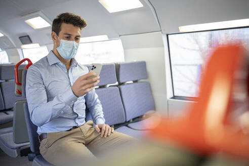 Businessman wearing protective face mask using mobile phone while sitting in train - IFRF00211