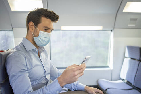 Mid adult businessman wearing face mask using smart phone while sitting in train - IFRF00214