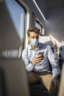 Businessman with protective face mask using mobile phone while sitting in train during COVID-19 - IFRF00217