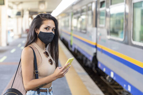 Young woman wearing face mask using mobile phone while standing on platform - WPEF03829