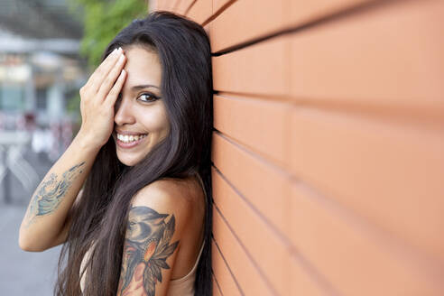 Young woman smiling while covering face with hand leaning on wall - WPEF03850