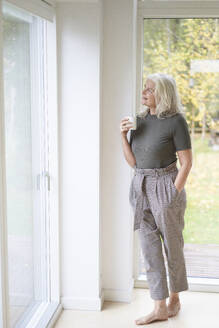 Thoughtful retired woman holding cup while looking through window at home - JAHF00046