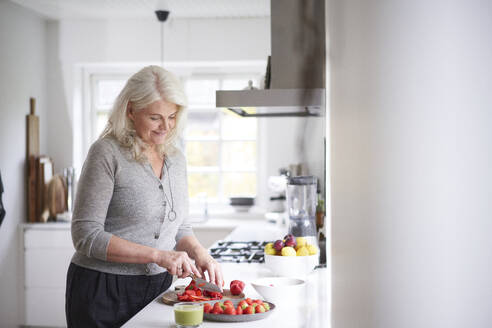 Retired woman cutting strawberries on board in kitchen at home - JAHF00052