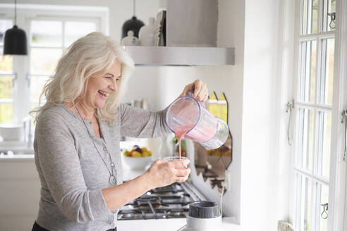 Cheerful senior woman pouring strawberry smoothie in glass at kitchen - JAHF00058