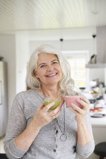Smiling retired woman holding fresh smoothies while standing in kitchen at home - JAHF00061
