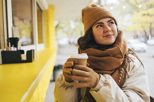 Smiling woman with disposable coffee cup day dreaming at street cafe during winter - OYF00299