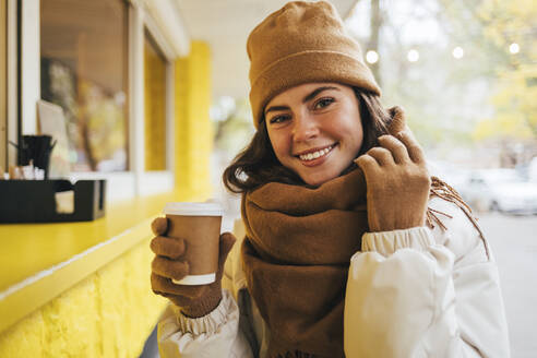 Smiling woman wearing scarf with disposable coffee cup at street cafe during autumn - OYF00302