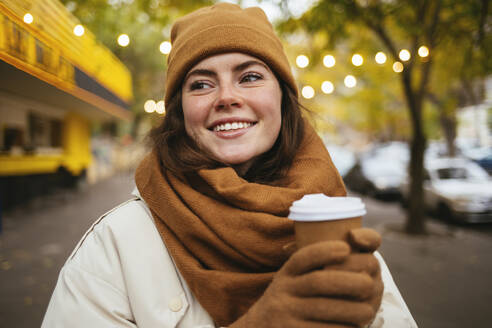 Smiling woman with disposable coffee cup looking away on sidewalk during autumn - OYF00305