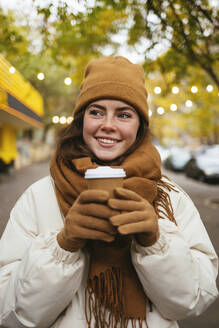 Smiling woman in warm clothing holding disposable coffee cup on sidewalk - OYF00308