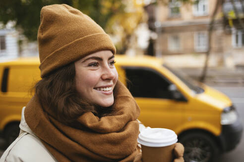 Smiling young woman with disposable coffee cup during winter - OYF00311