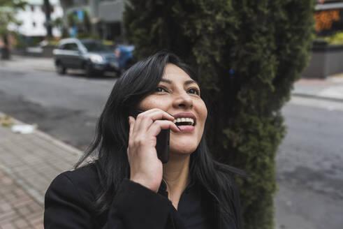 Happy woman talking on smart phone in city - DSIF00256