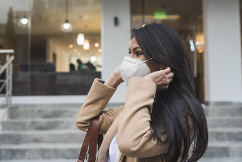 Woman wearing protective face mask standing by steps outside building during COVID-19 - DSIF00262