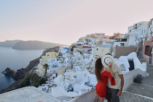 Loving traveling couple kissing at sundown while standing on balcony on Santorini and enjoying vacation together - ADSF19482