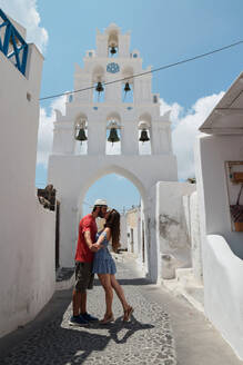 Side view of couple of tourists standing on old narrow street near church and tenderly kissing during summer vacation on Santorini - ADSF19485